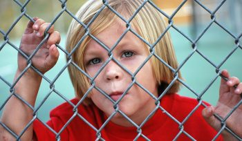 Photo of a boy looking through a fence representing a child with autism spectrum disorder whose parents are considering chelation therapy with a functional medicine doctor