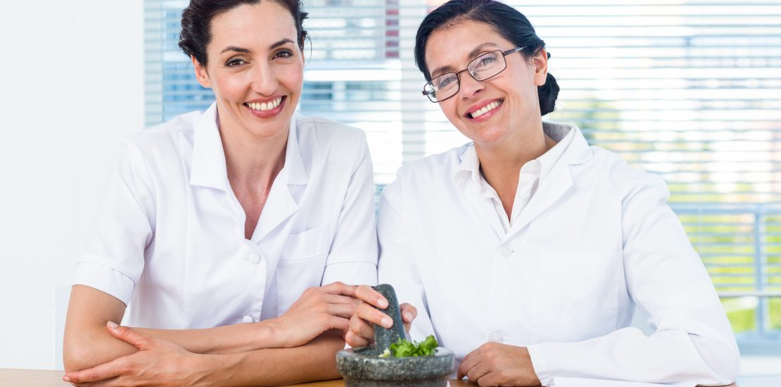 Photo of two doctors smiling after having prepared a personalized herbal concoction for patients at their functional medicine and holistic naturopathic practice